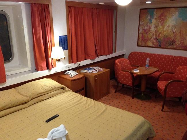 Cabine de luxe avec grand lit, coin salon et TV.